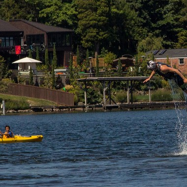 A curious kayaker watches as Mike Jeffery of AV Water Sports flyboards on Lake Washington. (Credit: Justin Steyer)