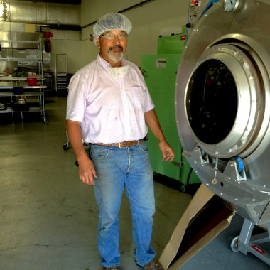 Richard Sakuma stands next to the panner, which is slowly spinning and roasting tea leaves.