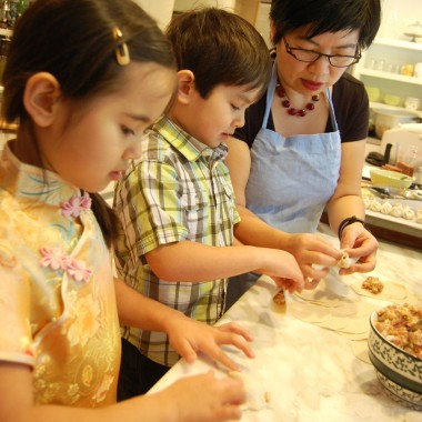Hsiao-Ching Chou watches as Shen, center, and Meilee, left pinch the dumplings shut. (Martha Kang/KPLU)