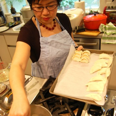 Hsiao-Chou Ching drops the dumplings into a pot of boiling water. (Martha Kang/KPLU)