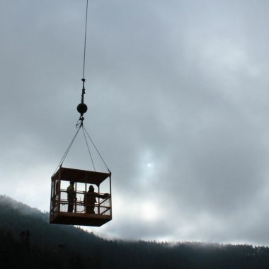 A man cage flies workers through the sky. (Courtesy of Rainey McKenna/Olympic National Park)