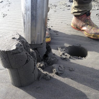"Gray uses his ""Clamhawg,"" a hefty sand-suctioning tool to dig out a clam. (Rae Ellen Bichell/KPLU)"