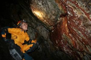 Mariana Tomas examines a cavern wall. (Martha Kang/KPLU)