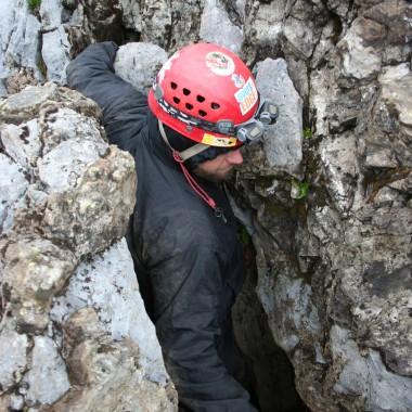 Tom Evans squeezes into Cascade Cave. (Martha Kang/KPLU)