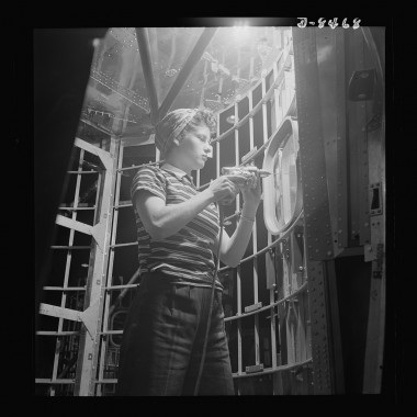 December 1942: A woman worker at the Boeing plant in Seattle helps to complete a fuselage framework. (Andreas Feininger/Farm Security Administration)