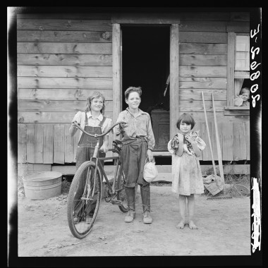 August 1939: Three of the four Arnold children. The oldest boy earned the money to buy his bicycle. Western Washington, Thurston County, Michigan Hill. (Dorothea Lange/Farm Security Administration)